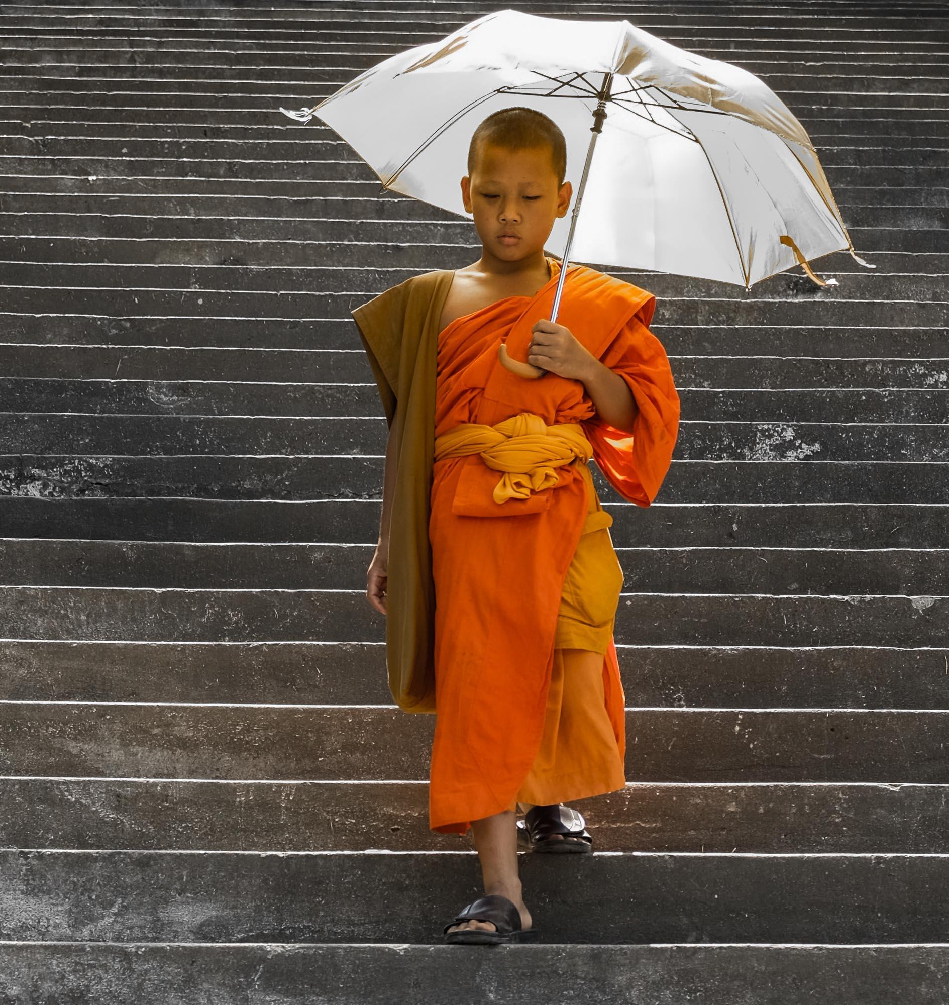 Ein junger Mönch auf einer Treppe in Luang Prabang, Laos