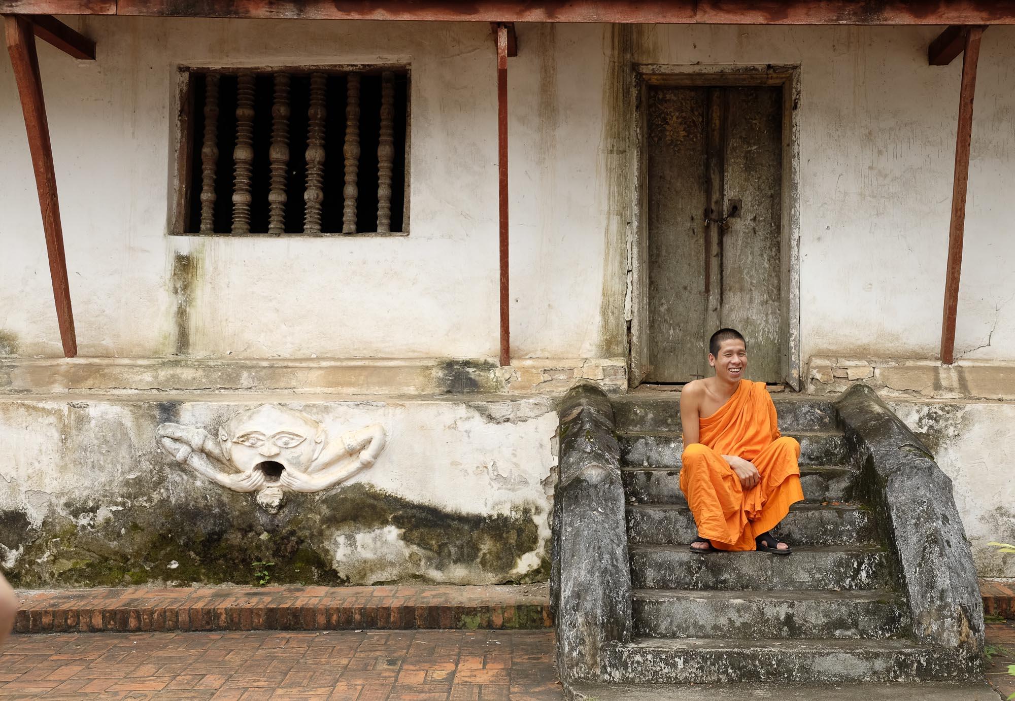 Ein lachender Mönch auf den Treppen vor seinem Kloster in Luang Prabang