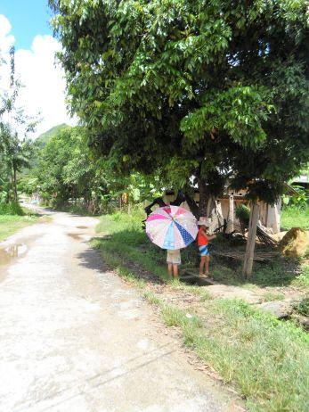 Bergwelt in Vietnam. Kinder unter Sonnenschirm.