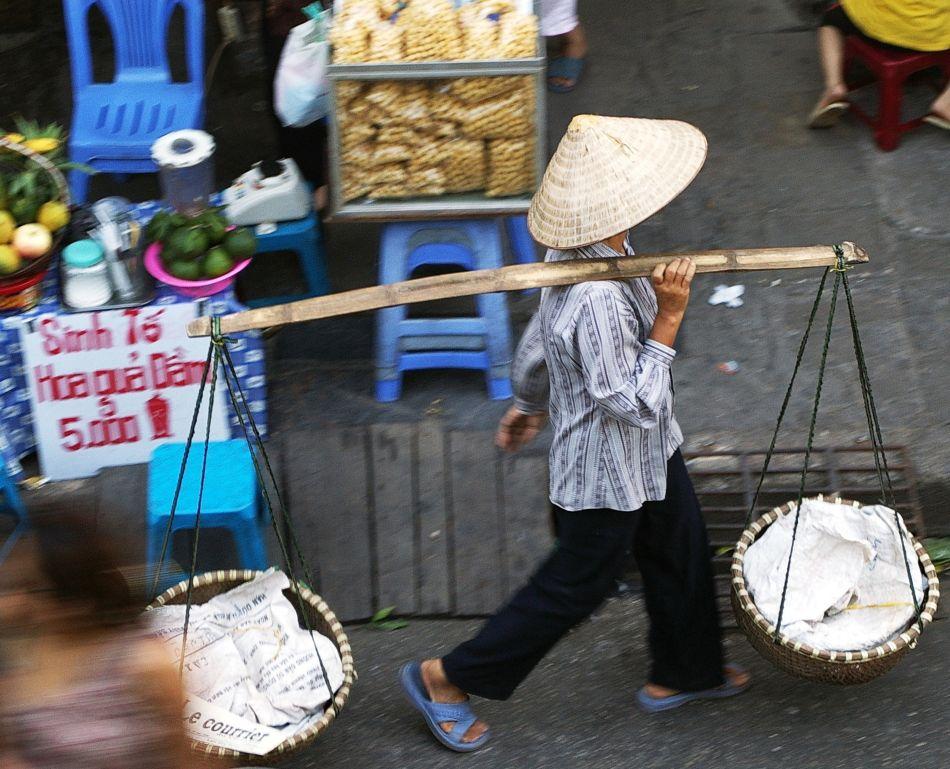 typisches Bild aus Vietnam Straßenverkäufer mit Reishut