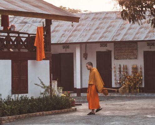 Laos ein Mönch vor einem Kloster